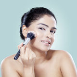 Woman applying makeup on her cheek Royalty Free Stock Image