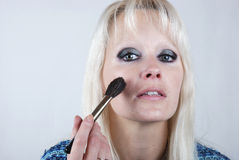 Woman applying makeup Royalty Free Stock Photography