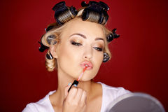 Woman applying makeup with her hair in curlers. Beautiful young woman applying makeup with her blond hair in curlers as she carefully applies lipstick while royalty free stock image