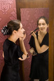 WOMAN APPLYING MAKEUP  looking in the mirror Royalty Free Stock Photos