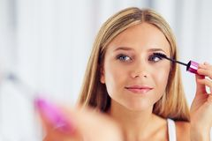 Woman applying makeup and looking in the mirror. Painting eyelashes with mascara royalty free stock photos