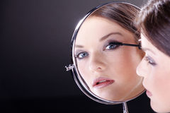 Woman with applying makeup with mirror Stock Photography
