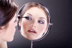 Woman with applying makeup with mirror Royalty Free Stock Photography