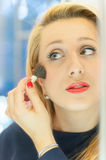 Woman applying makeup in the mirror stock photo