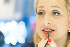 Woman applying makeup in the mirror royalty free stock photos