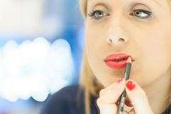 Woman applying makeup in the mirror. Woman who puts on lipstick in the mirror Stock Images