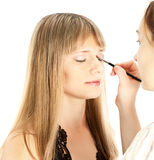 Woman applying makeup onto performer's face Royalty Free Stock Photography