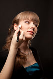 Woman applying makeup onto performer's face Royalty Free Stock Image
