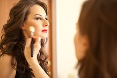 Woman applying makeup onto performer`s face Stock Photography