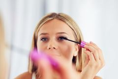 Woman applying makeup and painting eyelashes with mascara royalty free stock image