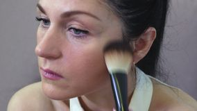 Woman applying makeup for perfect skin. In room stock video footage