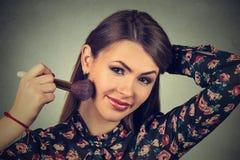 Woman applying makeup powder with brush Stock Image
