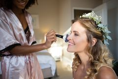 Woman applying makeup to bride in dressing room Stock Photography