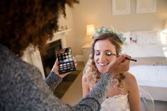 Woman applying makeup to bride in dressing room Stock Image