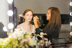 Woman applying makeup to model in salon Royalty Free Stock Photography