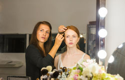 Woman applying makeup to model in salon Royalty Free Stock Photo