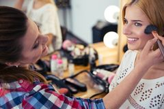 Woman applying makeup to model Royalty Free Stock Photography