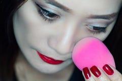 Woman Applying makeup. Using beauty blender Stock Photos