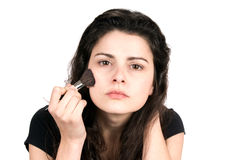 Woman Applying Makeup. Young woman uses a cosmetic brush to apply blush makeup to her face Royalty Free Stock Image
