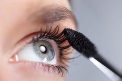 Woman applying mascara. On her eyelashes. Short depth of field Royalty Free Stock Photography