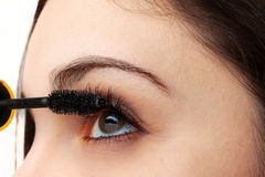 Woman applying mascara Stock Photos