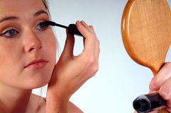 Woman applying mascara. Young woman gazing into a hand mirror whilst applying her mascara. Shot against a white background royalty free stock photos