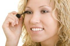 Woman applying mascara. Beautiful young blond woman applying mascara to her eyes, white background royalty free stock image