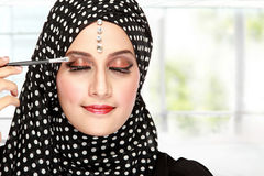 Woman applying mascara. Close up portrait of beautiful woman applying mascara on her eyelashes Royalty Free Stock Photo
