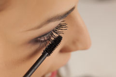 Woman applying mascara. Close up of a young woman applying mascara to her eyelashes Royalty Free Stock Photography