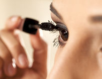 Woman applying mascara. Close up of a young woman applying mascara to her eyelashes Stock Images