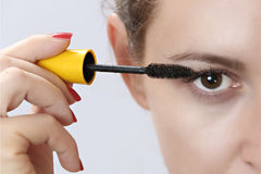 Woman applying mascara on eyelashes Royalty Free Stock Photo
