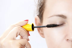 Woman applying mascara on eyelashes Royalty Free Stock Photography