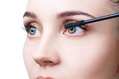 Woman applying mascara on eyelashes with brush. Young woman applying mascara on eyelashes with brush. Isolated on white Royalty Free Stock Photography