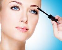 Woman applying mascara on eyelashes with makeup brush Stock Image