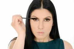 Woman applying mascara on eyelashes with makeup brush. Isolated on white background Stock Images