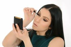 Woman applying mascara on eyelashes with makeup brush. Woman holding mirror. Beautiful woman isolated on white background Royalty Free Stock Photography