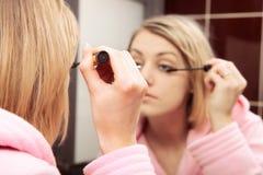 Woman applying mascara on eyelashes Stock Image