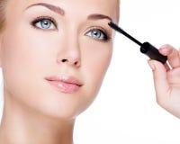Woman applying mascara on eyelashes Royalty Free Stock Photography
