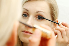 Woman applying mascara in front of mirror Royalty Free Stock Photos
