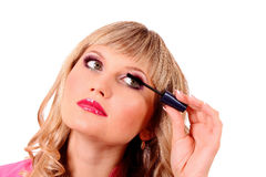 woman applying mascara on her eyelashes Royalty Free Stock Photo