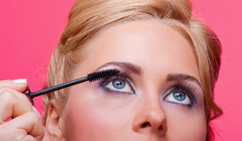 Woman applying mascara on her eyelashes Royalty Free Stock Images