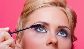 Woman applying mascara on her eyelashes. Beautiful woman applying mascara on her eyelashes Royalty Free Stock Images