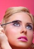 Woman applying mascara on her eyelashes Stock Images