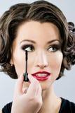 Woman applying mascara on her eyelashes. Woman applying mascara on her long eyelashes Stock Photos