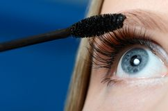 Woman applying mascara on her eyelashes - macro shot Stock Photo