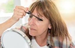 Woman applying mascara on her eyelashes. Mature woman applying mascara on her eyelashes Royalty Free Stock Photography