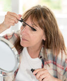 Woman applying mascara on her eyelashes. Mature woman applying mascara on her eyelashes Stock Photo