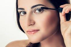 Woman applying mascara. On her long eyelashes Stock Photos
