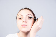 Woman Applying Mascara While Looking at the Camera Royalty Free Stock Photos