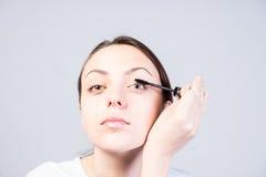 Woman Applying Mascara While Looking at the Camera Royalty Free Stock Photos